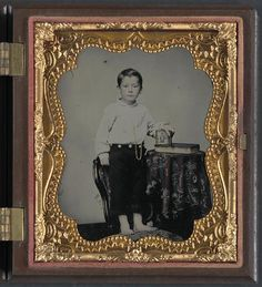"""Unidentified boy holding cased photograph of soldier in Confederate uniform atop a Bible,"" by Charles R. Rees, sixth-plate ambrotype, hand-colored (Library of Congress)."
