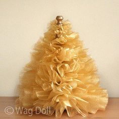 Bridget from Wag Doll shows how to make a gathered tulle mini Christmas tree. The fluffy, sparkly tree would be gorgeous on a mantel or as part of a holiday tablescape. It's cleverly built a…