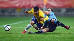 Danilo (L) of Brazil is challenged by Diego Poyet of Uruguay