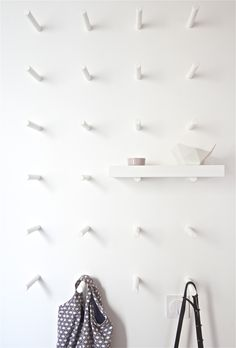 a wall of pegs: hang things from them, use a piece of wood to turn them into shelves. Peg Wall, Decoration Entree, Interiores Design, White Walls, Home Organization, Organizing, Interior Inspiration, Interior And Exterior, Home Accessories