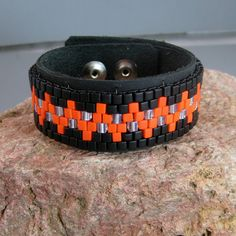 This beaded Leather bracelet sports a Native American design in orange and black. Very bright and festive! The Miyuki 4 mm beads are stitched