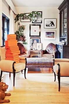 Stylish gallery wall, antique leather chairs, and rich textiles in this sitting room