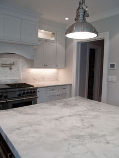A super white granite for island and countertops with carrara marble on