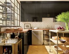 Contemporary Kitchen by Nate Berkus in New York, New York -- love the sleek, contemporary BRASS hardware against black lacquered cabinets, mixed with stainless steel and brushed nickel