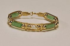 "This bracelet is made using Jade, accented by Pearl and gold beads. Each stone is separated from the next by 14k Gold artist wire and framed in small gold wire ""windows"