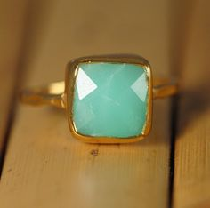 "A Chrysoprase Cushion cut gemstone bezel set in 18k gold vermeil with a hand hammered band.   Details: Gemstone: Chrysoprase Stone Cut: Cushion Cut Stone Size: Approximately 9 mm (0.35"") Metal: 18K Gold Vermeil (18K Gold plated 925 Sterling Silver) Because natural stones are used, the stones may vary slightly in shape, size and color.   Size Chart: US Size    UK      European    Circumference (mm) 4            H 1/2       46.5                46.7 5            J 1/2         49             …"