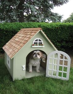 """STORYBOOK DOG COTTAGE Craftsman-style side window offers a view of squirrels and rabbits while a flower box charms a pooch haven roomy enough for a 40lb. dog. Dog bone latch secures the door. Shingled roof, non-toxic paint, ventilation and drainage. Simple assembly, 29 x 32 x 29"""" White or green."""