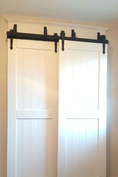 The raised-panels on these white barn doors with the contrasting hardware gives a classic look to the space.