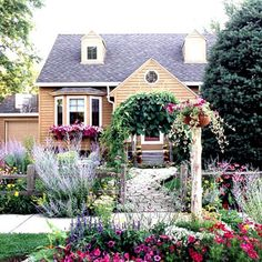 Colorful Cottage Charm  Bright flowers go a long way in creating cottage charm. Here, colorful plantings by the street mimic the flowers overflowing from the home's window boxes. A vine-covered arbor invites visitors to pass through and follow a gently curving pathway to the front door.