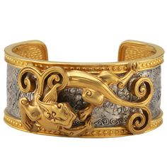 Tibetan Dragon Cuff - The vibrant dragon design on our bracelet is based on a Tibetan motif adapted from a pair of plates of an eighteenth century saddle. The original plates are notable for their delicate pierced work, the inlaying of gold and silver, and the unusual archaic style of the dragons on each plate, which are distinguished by a short feline snout, a single horn, a split tendril emerging from behind the head, a long curving body, catlike limbs, and a curling split tail.