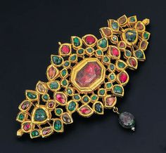 A GEM-SET SARPECH   The openwork foliate panel set with cabochon rubies and emeralds within foiled surrounds suspending a tourmaline bead, the engraved reverse depicting floral motifs, early 20th century, 11.0cm wide, in fitted case by Mortimer and Hunt, (brooch fitting later adapted)