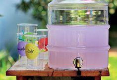Boa ideia para uma festa de criança: o suco fica neste recipiente de vidro, que lembra um filtro. Personalize os copos com os nomes dos convidados, amarrando um cartão em volta deles