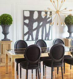 idea para decorar comedor con lámpara sputnik dorada y sillas luis xvi negras