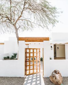 such a beautiful way to do modern Mediterranean home. white plaster, succulents,… such a beautiful way to do modern Mediterranean home. white plaster, succulents, beautiful rocks and wood gate make a beautiful entry into this spanish style home Spanish Bungalow, Spanish Style, Cabana, Exterior Design, Interior And Exterior, Modern Mediterranean Homes, Villa, Front Gates, Desert Homes