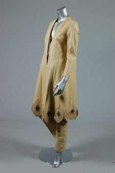 John Jones ivory leather 'peacock feather' ensemble, 1981, initialled and dated to the trouser waistband, the coat with gored plume panels, silver quill sections, coloured suede and gold leather cutwork tips, ties to fasten; matching tapered trousers