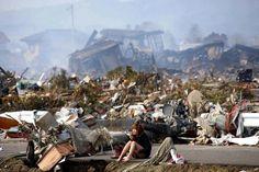 Una donna siede sulle macerie dopo lo tsunami che colpì il nord del Giappone nel 2011
