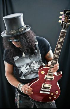 Slash (born July a British-born American musician and songwriter. He is best known as the lead guitarist of the American rock band Guns N' Roses, with whom he achieved worldwide success in the late and early Guns N Roses, Saul Hudson, Rock Y Metal, Velvet Revolver, Rock Poster, Best Guitarist, Gibson Les Paul, Gibson Lp, Rock Legends