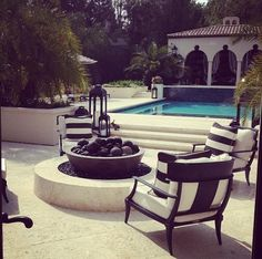 Black and white chairs surrounding firepit.