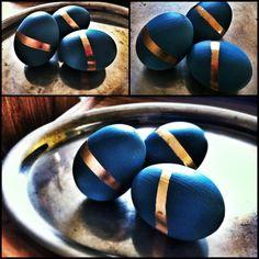 Ei mit Acyl-Farbe grundieren.  Nachdem die Farbe getrocknet war, klebte ich die Eier ab, sodass Streifenkringel ums Ei herum frei blieben. Ich bestrich bei einem Teil der Eier die freien Stellen mit Leim & bestäubte sie anschließend mit Glitzer. Den anderen Teil besprühte ich mit Goldlack. Nachdem die Farbe/der Leim getrocknet war, konnt ich das Abklebeband entfernen & die Eier aufhängen bzw. verschenken.