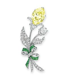 A COLORED DIAMOND, DIAMOND AND GARNET BROOCH   Designed as a floral bouquet, set with a marquise-cut fancy intense yellow diamond, weighing approximately 13.63 carats, to the old European-cut diamond buds and leaves, gathered by calibré-cut demantoid garnet ribbons, mounted in white gold