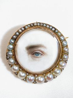 "1830s Lover's eye miniature portrait brooch - ""The most enigmatic and often elusive of jewels is the lover's eye or eye miniature....However, contrary to some beliefs, these eye miniatures also became tokens of affection between family and friends, and even became memorial pieces."" Found via The Three Graces"