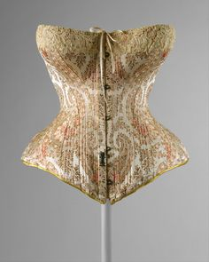 Corset ca. 1891 via The Costume Institute of The Metropolitan Museum of Art    The hook seen on the front of this corset and on other was there for the purpose of keeping skirts, petticoats, and other various underthings from riding up.