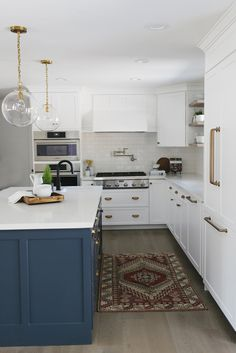 White kitchen design with navy island cabniets and brass accents | House of Jade