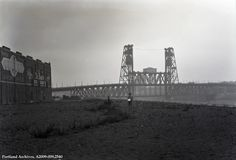 Steel Bridge, 1930. The number man is standing close to the Harbor Wall near Davis St., with the Steel Bridge in the background to the north. The structures on the left side of the image are on Front Ave.