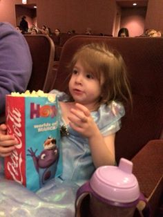Loving her popcorn at the movies.