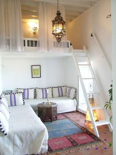 Everything about this little loft space is perfect, from the curtains giving privacy, to the hanging lamp, to the downstairs rug. Love.