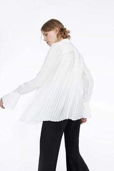 This white blouse knows how to balance both work and play. Pleated at the back, this tie-neck blouse has a comfortable oversized fit and high-low hem line.