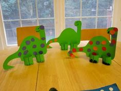 Dinosaur cut from a cereal box. Paint & decorate with construction paper circles. Use TP tube cut in half and slit for feet.