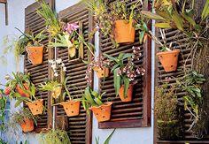 As venezianas de madeira sobraram na reforma e foram transformadas em painéis de parede para a coleção de orquídeas. Passe nelas uma demão de verniz para que aguentem mais as intempéries. Prenda-as com parafusos na parede, plante as orquídeas em vasos meia-lua e use ganchos para pendurá-los