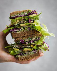 vegan veggie sandwich with avocado, cucumber, spinach. lettuce & parsley tahini