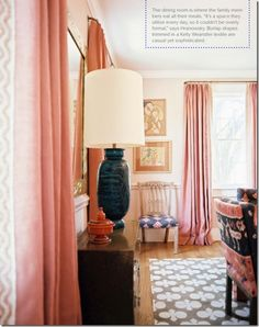 coral pink drapes on light pink walls- somehow though, it doesn't feel super girly.  My guess is the bold print chairs, rug and lamp