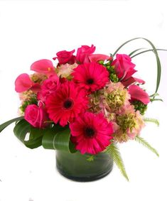 Pretty In Pink - Capture the essence of true love with this stunning bouquet presented in a sleek leaf lined glass vase. Hot pink roses, calla lilies and cheery gerbera daisies are nested with lush hydrangea and mixed foliage. #KittelbergerFlorist #RochesterFlowers