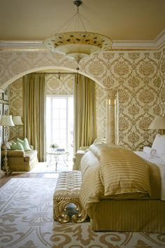 Tobi Fairley design.   White and gold wall paper and area rug in a traditional style bedroom.