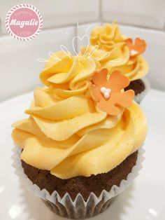 Chocolate cupcakes with orange frosting and a delicate touch on top.
