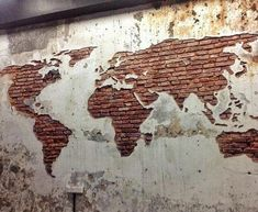Concrete and brick wall make up this world map wall design. Metal beam above. All of them are materials for Industrial Design and related styles. Map is a reference to travel, which is also an element of the style. - Welcome My Decor