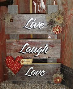"Handmade reclaimed barn wood ladder wall or floor sign that reads ""live laugh love"". It was made from a barn that was falling down this past summer. A coat of protective sealant was added over the words and also brings out the great texture in the barnwood. It's decorated with Americana homespun flowers adorned with buttons, spanish moss, rusty bells and a primitive heart. This sign is made very sturdy and will last forever. Measures 21"" H x 14"" W."