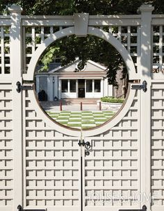 "Boost the appeal of your home by framing the view from the street with an interesting gate. This ""moon gate"" draws the eye to the striking checkerboard lawn and classically designed summerhouse beyond. 