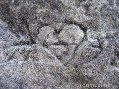 A heart and arrow carved into a stone at the top of a cliff.