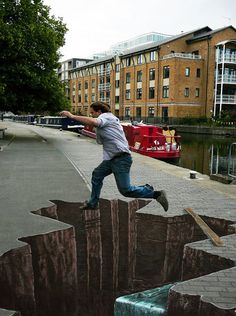 Street art, those are so cool, he literally look like he's jumping over a canyon... So talented!!!