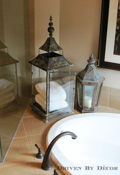 A large lantern as a unique spot to store towels by the bathtub
