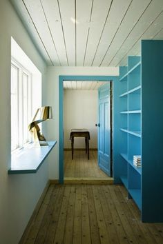 summer house in Southern Sweden, house is white with black roof, interior mostly neutrals with punctuation of this bright blue on stairs, doors, & bookshelves-a great colour with white & pine