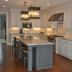 White cabinets & dark grey island; lanterns above island