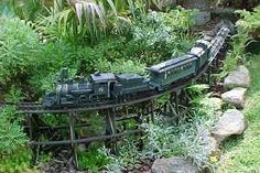 Garden railway setting with raised track, loco, carriages and landscaping with appropriate rocks, plants etc. to make a realistic and delightful layout which merges into the overall design of the garden.