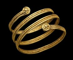 An Etruscan Gold Sprial ring circa 7th Century BC. Composed of two smooth wires either side of a spirally twisted wire, terminals in the form of granular rosettes within a wire border.