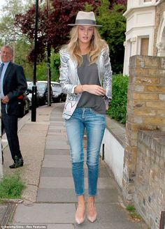 Off-duty chic: Supermodel Rosie Huntington-Whiteley brightened up the dreary day in a metallic print jacket and fedora as she headed to a friends house in London on Tuesday
