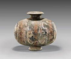 """HAN DYNASTY POTTERY COCOON JAR with remains of brightly pigmented geometric designs; the egg-form with flared rim and on a slightly splayed foot; L: 11"""""""